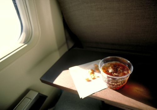 Soda y maní en la bandeja del asiento del avión