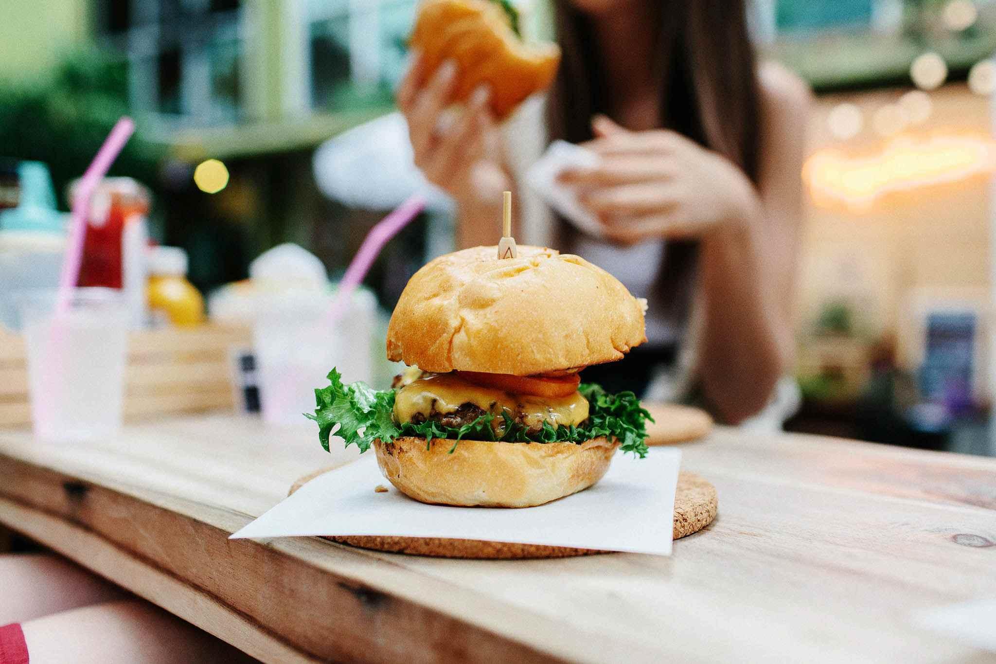 Primer plano de la hamburguesa con una mujer sentada en segundo plano en el restaurante