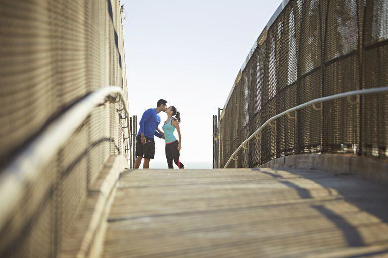 Joggers kissing on a bridge