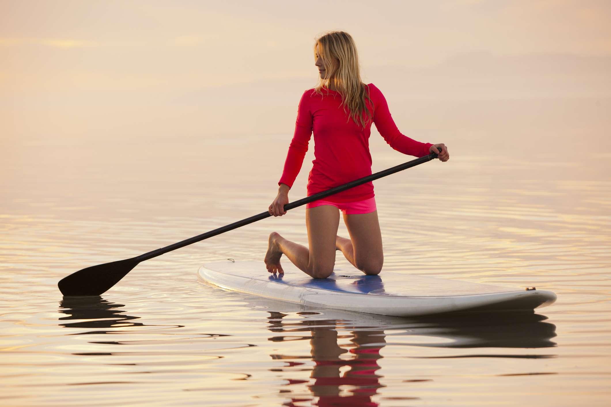 Mujer arrodillada sobre paddleboard