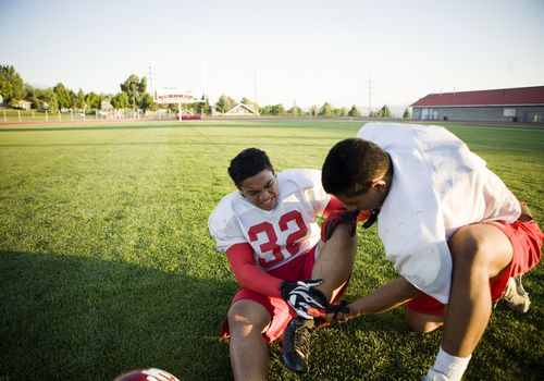 Teammate helps injured football player check hurt ankle