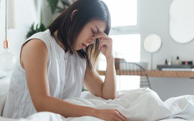 Young Woman Suffering Headache In Bed - stock photo