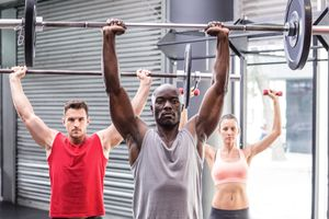 Three athletes perform a barbell overhead shoulder press.