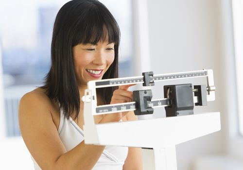 Smiling woman checking her weight