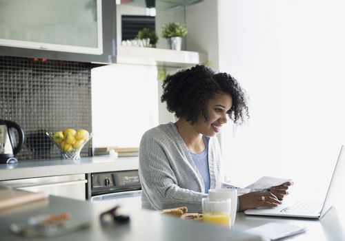 Woman sitting in the kitchen working at her laptop
