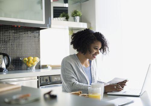 Mujer sentada en la cocina trabajando en su computadora portátil
