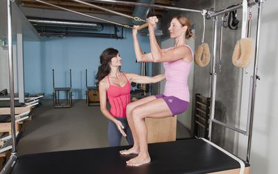 woman doing pilates with trainer