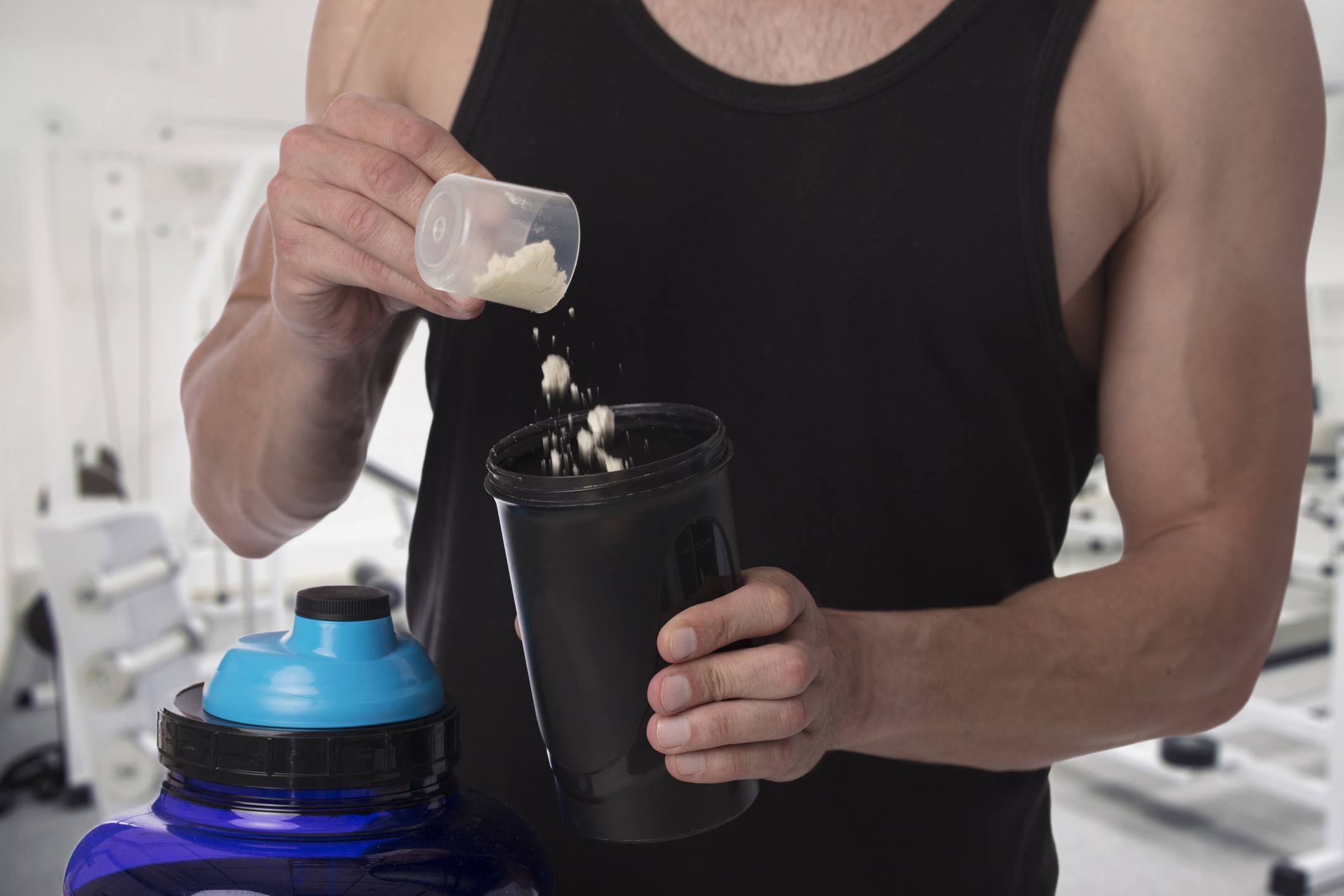 Man putting creatine powder into shaker cup at the gym