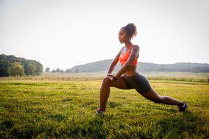 Young female runner stretching hip flexor in rural park