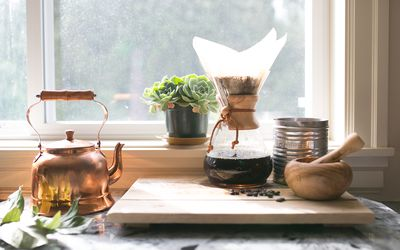 Eye-level view of Coffee and Kettle and Succulent - stock photo