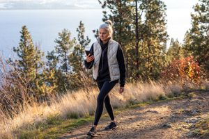 woman walking in woods and checking mileage on phone
