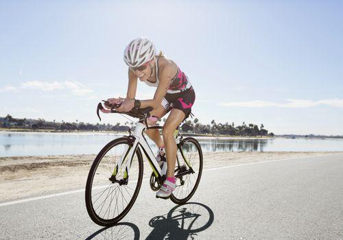 Ciclista femenina montando bicicleta en la carretera cerca del lago