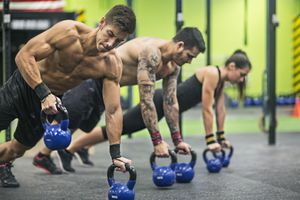 two men and a woman doing rows with kettlebells