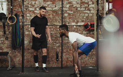 A trainer teaching an athlete how to do a barbell movement.