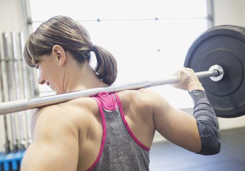 Mujer con barra sobre sus hombros