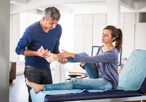 physical therapist looks at woman's ankle
