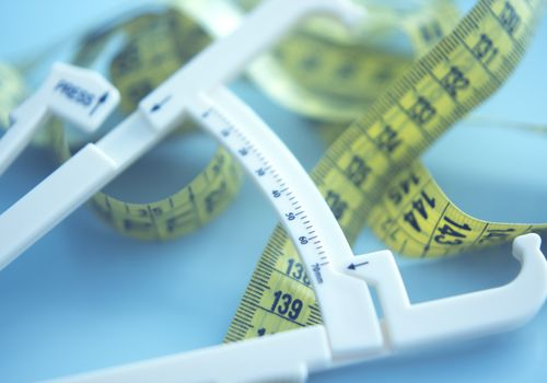 Fat caliper and measuring tape used to measure waistline, bodyfat levels for fitness and obesity check