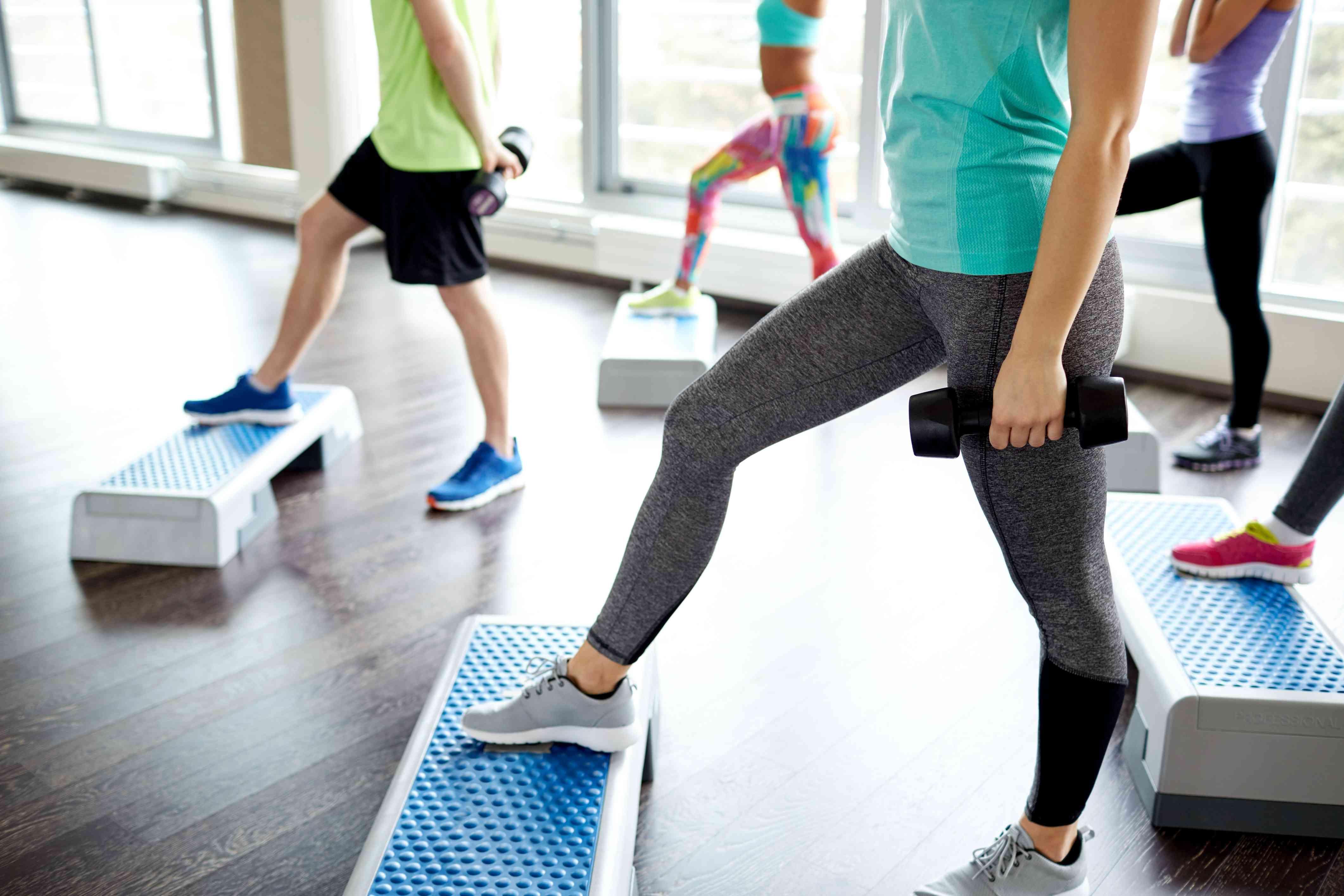 Grupo de personas con pesas haciendo step-ups en entrenamiento de circuito