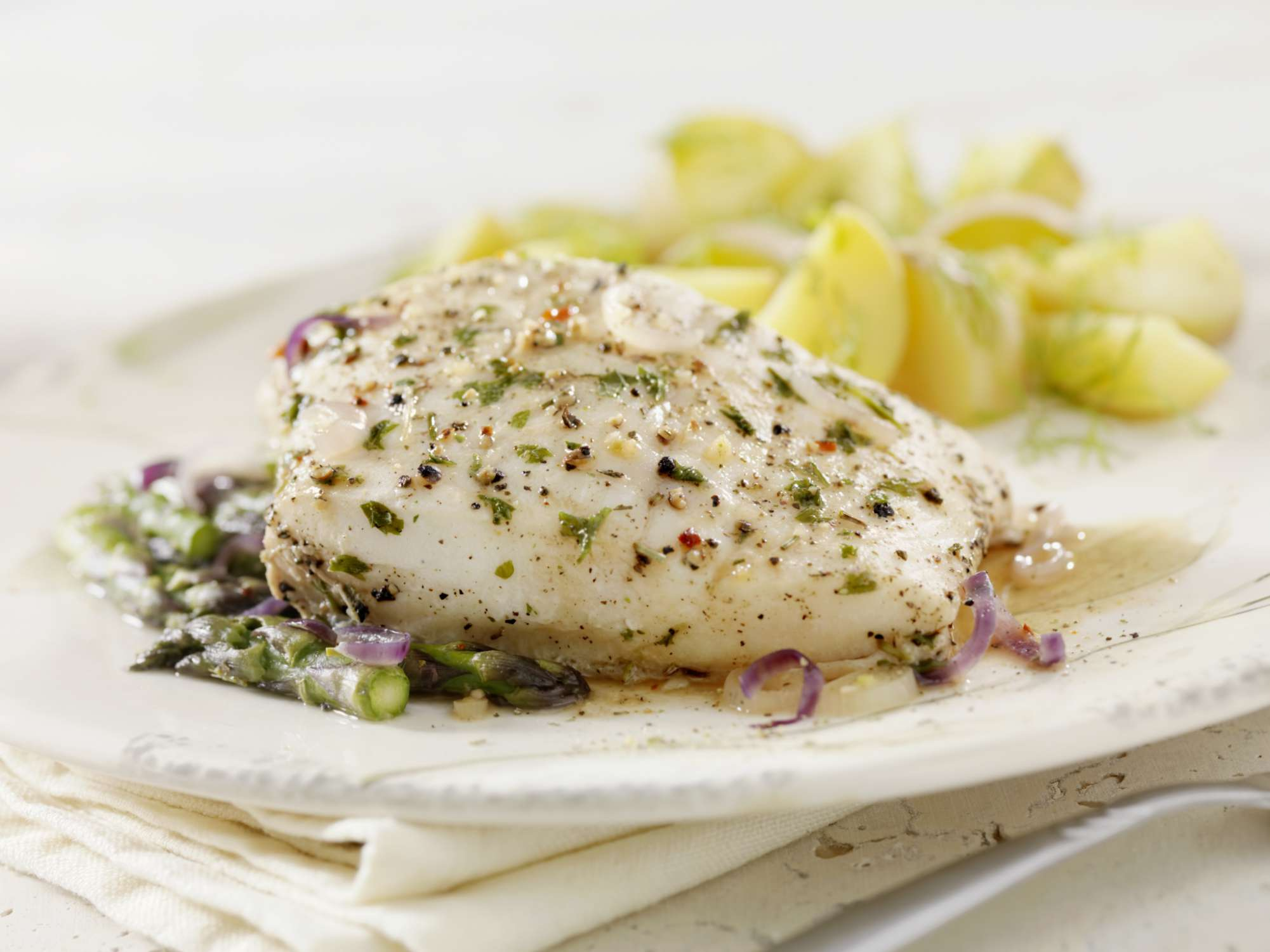 poached white fish on a plate with herbs and asparagus tips