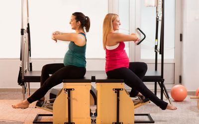 Two smiling pregnant women exercising on Pilates stability chairs.