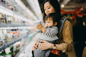 mother holding baby who is holding a yoghurt container