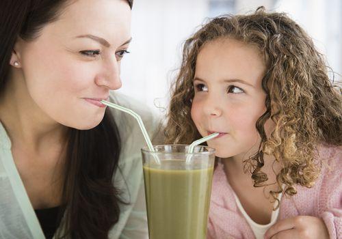 Niños comiendo verduras - madre hija bebiendo batido verde