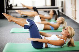 Three women doing Pilates mat exercises