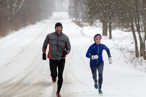 Male and Female running sprinting up a snowy hill during a winter training run