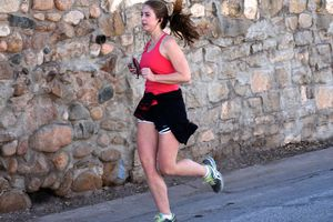 A young woman uses her smartphone as she jogs along a road in Santa Fe, New Mexico.