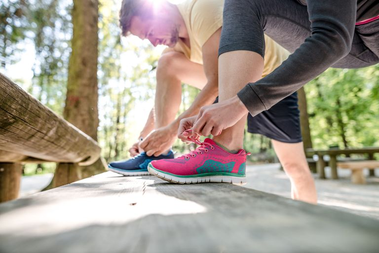 Woman and man tying sneakers outdoors