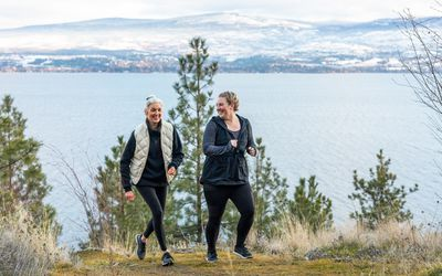 two women running together in the mountains in the winter