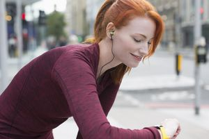 Smiling female runner with red hair and headphones checking smart watch