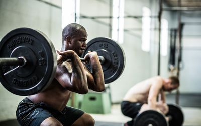 A man performs a front squat in a CrossFit gym
