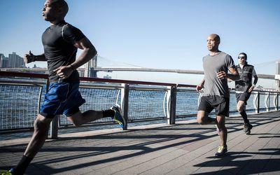 Runners running along a river