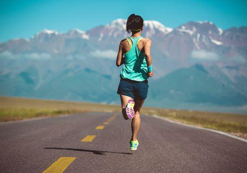 Vista trasera del corredor de fitness mujer corriendo en carretera