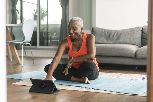 A black senior woman takes an online yoga class