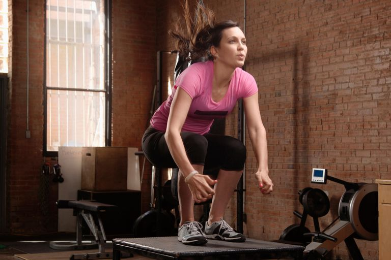 Young woman performing squat jumps in gym