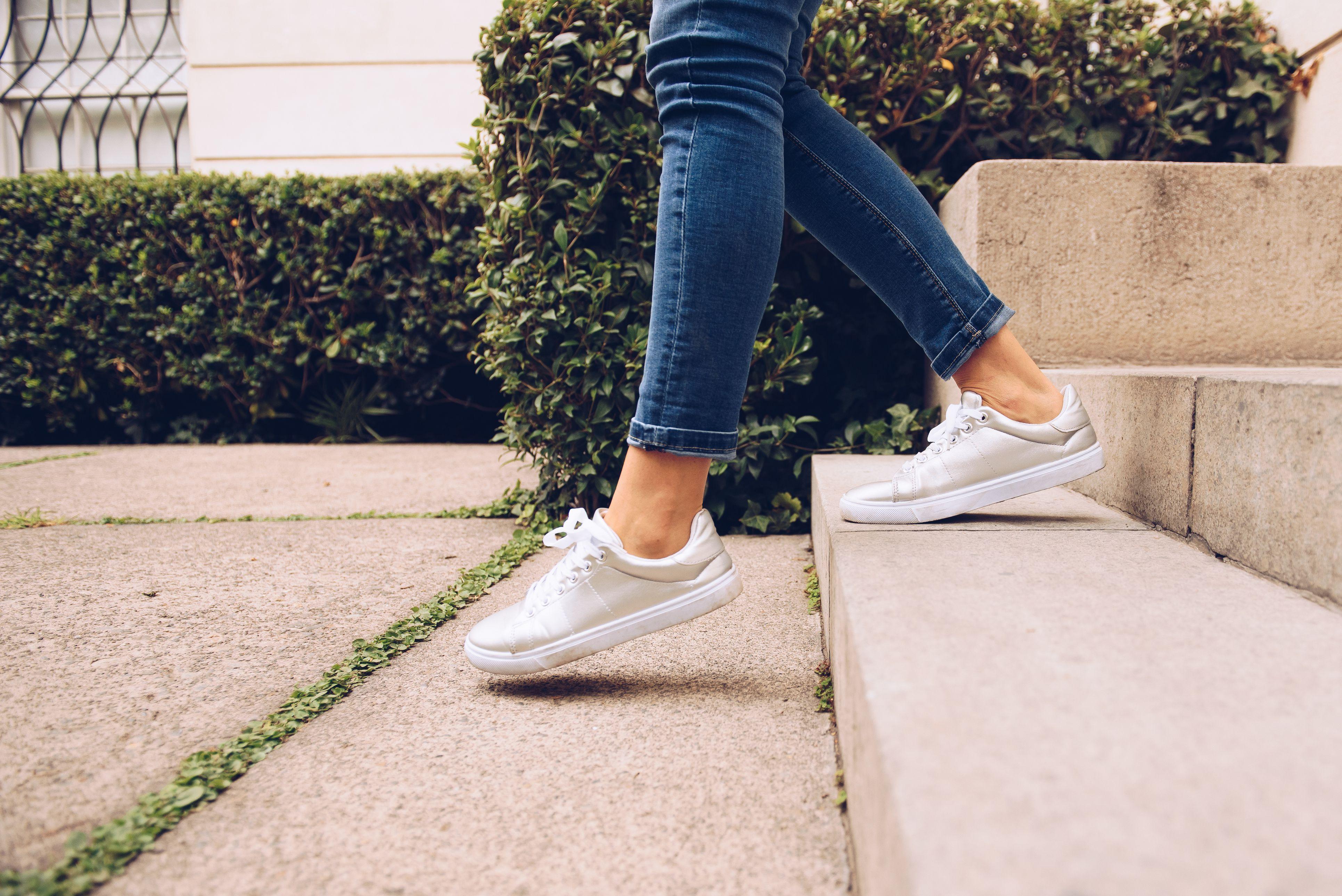 Piernas de mujer vistiendo zapatillas caminando abajo