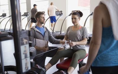 Personal trainer guiding woman seated cable row gym