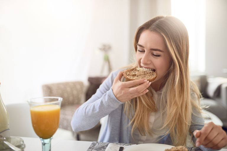 Blonde-haired girl eating wheat bagel and drinking orange juice for breakfast