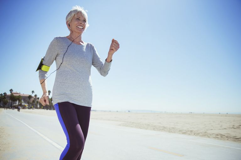 Senior woman jogging on beach boardwalk