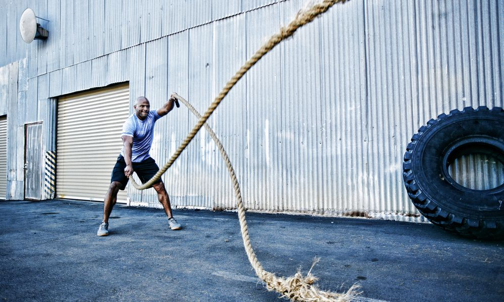 A man doing physical fitness exercises with battle ropes outside of a warehouse-style gym.