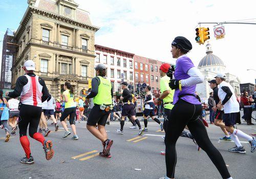corredores de maratón cruzando la calle de la ciudad