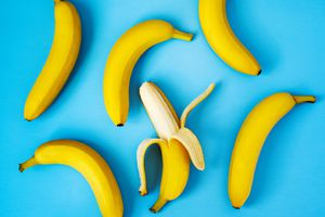 Six bananas, one peeled, on a bright blue background