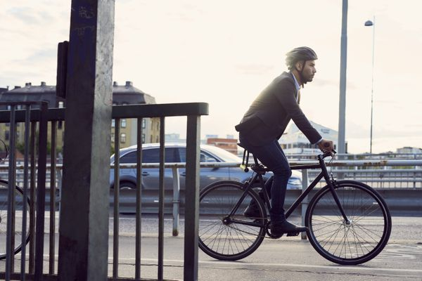 Side view of businessman cycling on street against sky