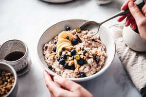Woman making healthy breakfast in kitchen