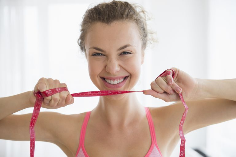 Happy woman with a measuring tape