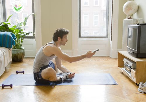 Man stretching and operating TV during workout