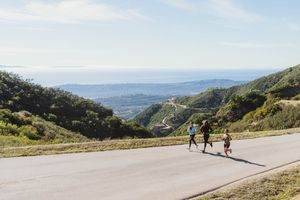three people running up a hill in the mountains
