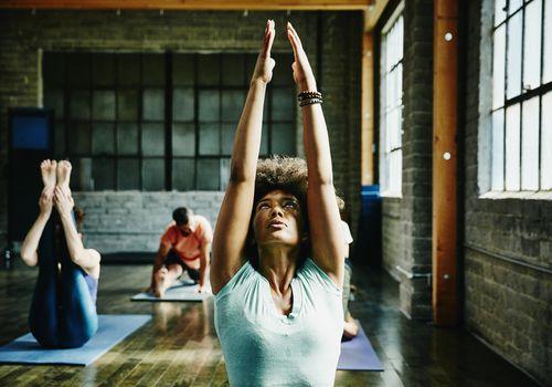 Mujer calentando para clase de yoga en estudio
